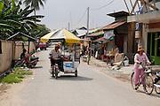 Verkopers rijden door een straat in Phnom Penh.