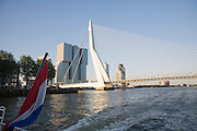 Dutch national flag flying at the back of a boat with buildings of De Rotterdam and Erasmusbrug in the background, Rotterdam, Netherlands