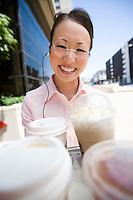 Portrait of young woman with take-away coffees, outdoors