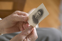 Old ladies hands holding an old black and white small photo