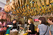 Shoppers in butcher's shop to buy Iberico Jamon Ham and other meats in Calle de Bidebarrieta in Bilbao, Spain