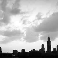 Chicago skyline panorama silhouette photo in black and white. Panorama photo ratio is 1:3 and has a backlit Silhouette of downtown Chicago with dramatic clouds. Picture includes Willis Tower (Sears Tower) and many other Chicago city buidlings.