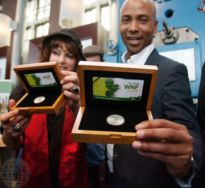 Ellen ten Damme en Humberto Tan tonen het 50 jaar WNF vijfje. Bij de Munt in Utrecht slaan Humberto Tan en Ellen ten Damme, beide ambassadeurs voor het WNF, de eerste slag van een muntje ter ere van het vijftig jarig bestaan van het Wereld Natuur Fonds. De munt is ontworpen door Willehad Eilers.<br /> <br /> At the Munt in Utrecht Ellen ten Damme and Humberto Tan, both ambassadors of the Dutch WWF, are pressing the first example of a special Euro coin to celebrate the fiftieth birthday of the World Wildlife Fund.