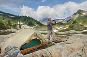 Man taking pictures with smartphone at backcountry campsite. Yellow Aster Butte Basin, Mount Baker Wilderness. Mount Shuksan is in the distance. North Cascades Washington