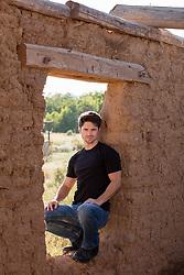 man in an adobe window frame