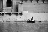 A woman rows a boat along the Ganges river in Varanasi, India