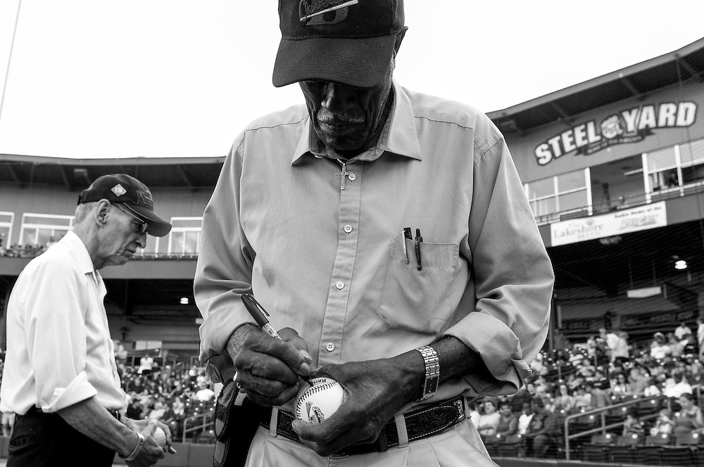 "Former Negro League player Hank Presswood, center, and Johnny Washington, left, sign baseballs at the ""Steel Yard"" minor-league baseball stadium in Gary, Indiana. The city of roughly 80,000 was founded in 1906 by the U.S. Steel Corporation as the home for its new plant. But in the 1960s Gary's fortunes, so closely linked to the steel industry, took a downturn. Businesses closed and the crime rate spiraled earning Gary the infamous distinction of ""Murder Capital of America."" (© William B. Plowman/Redux)"