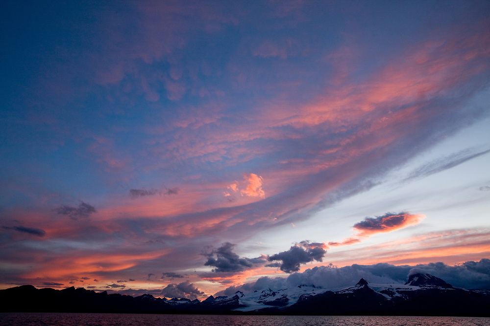 USA, Alaska, Katmai National Park, Midnight sun lights clouds above mountains along Hallo Bay at sunset on summer evening