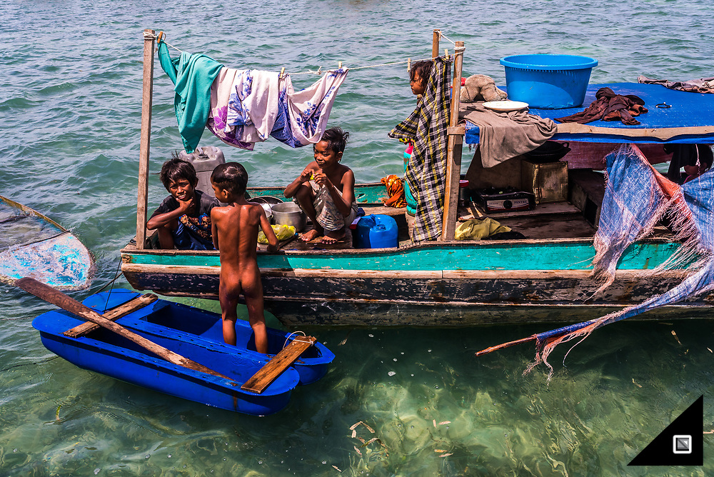 """Sea Bajau who live within a basic setup on their handmade houseboats (called lepa lepa). Just essentials are needed. Such as fishing and cooking gear as well as one outfit each family member, mostly families up to 5 live on one boat. """"Rather you than me"""", would be the general thought one comes up with when observing the spartan life of the Sea Bajau. To my surprise, some I've been chatting to, think the same when watching holidayers passing by. Many Bajau Laut prefer to continue the nomadic way of life and are just happy with what they have. Spontaneously, the families leave their boats and go ashore to trade their extra seafood (mainly fish, lobster, and sea cucumber) to nearby islanders. In return, they will stock up their essentials, collect water or buy cassava for the typical dish called Kasaba Panggykayu. Before sunset, everyone is back on the houseboat again, where communal cooking takes place."""