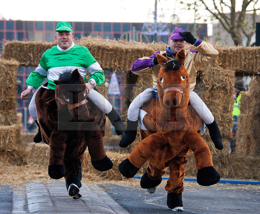 © under licence to London News Pictures 28/11/2010 today picture. Birmingham`s wackiest Christmas event, the annual Pantominme Horse Grand National. The event that sees riders and horses race up and down Broad Street in the City Centre jumping over and even Through straw bales. Pictures shows riders racing through the straw bales..Picture credit: Dave Warren/London News Pictures...
