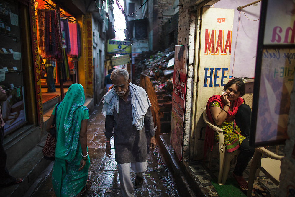 Woman talking on the phone in a shop while people pass on an alley in Varanasi, in India.