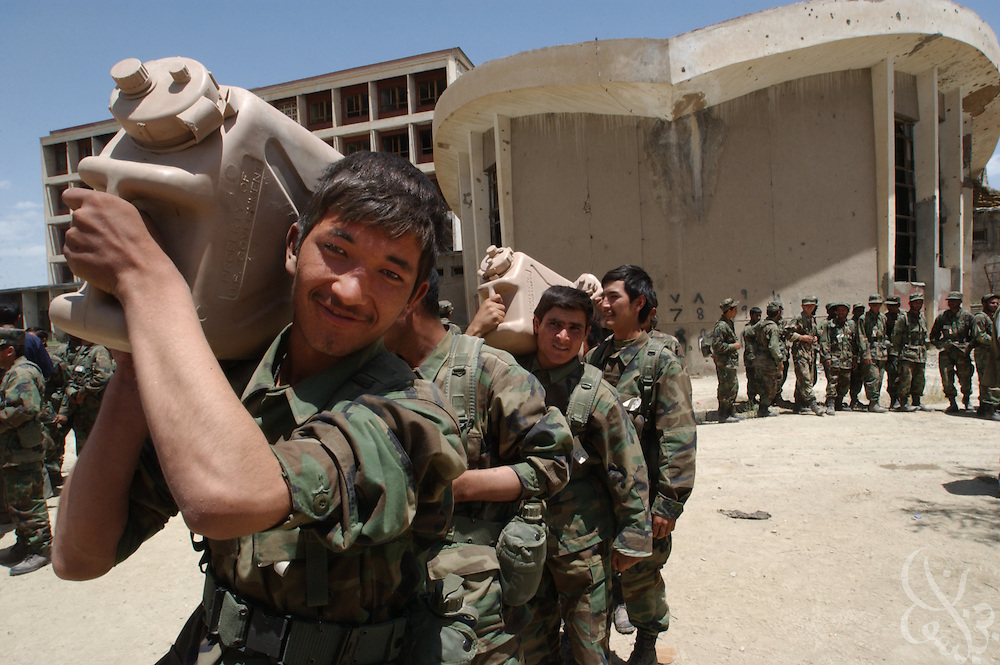 Afghan National Army (ANA) soldiers carry 45 pound water jugs as part of an obstacle course at their training facility May 27, 2002 in Kabul, Afghanistan. U.S. Special Forces conduct ten week training courses for the Afghan Army in the hope that a better trained military will mean a more stable Afghanistan.