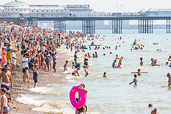 © Licensed to London News Pictures. 25/08/2019. Brighton, UK. Thousands of people take to the beach and in Brighton and Hove on the August Bank Holiday Sunday as hot and sunny weather is hitting the seaside resort. Photo credit: Hugo Michiels/LNP