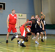 UK - Tuesday, Nov 18 2008:  Jonny Lee (#12) watches Erks guard Keith Pringle drive to the basket during the first half of Barking and Dagenham Erkenwald Basketball Club's Essex Basketball League game against Brightlingsea Sledgehammers. Erks won the game 91 - 86. (Photo by Peter Horrell / http://www.peterhorrell.com)