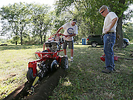Cal Schultz (from left) and Pat Welsh, both of Cedar Rapids, work on digging a trench for an electrical outlet at a campground near Bertram on Tuesday afternoon, May 29, 2012. (Stephen Mally/Freelance)
