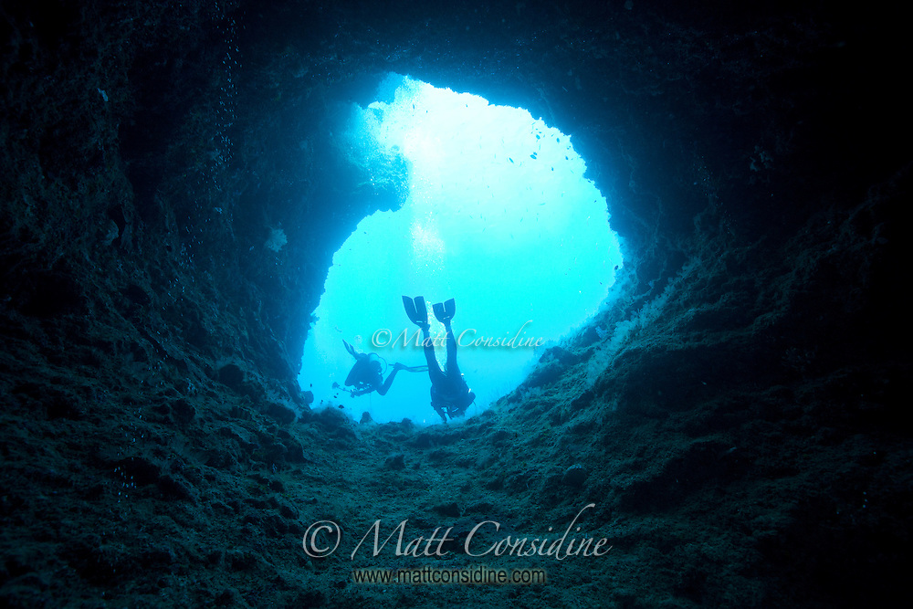 Looking up at divers and the sky through one of the entrances to Blue Holes, Palau Micronesia. (Photo by Matt Considine - Images of Asia Collection)