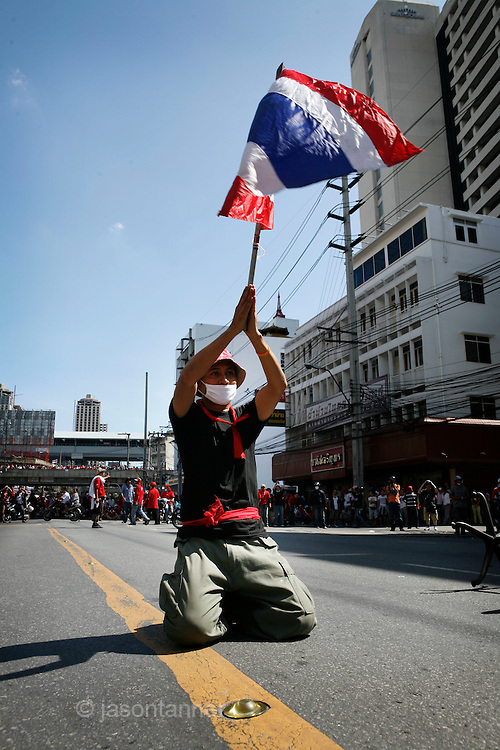"A ""red Shirt' supporter taunts police and military forces on the streets of bangkok waving the national flag of Thailand...Violence between the 'Red Shirts' of the UDD and police / government military forces on the city streets of Bangkok. The UDD (United Front for Democracy Against Dictatorship) says Prime Minister Abhisit Vejjajiva came to power illegitimately and is a puppet of the military. The movement is made up of supporters of former Prime Minister Thaksin Shinawatra who was ousted in a coup in September 2006. The UDD wants Mr Abhisit to resign and call fresh elections."