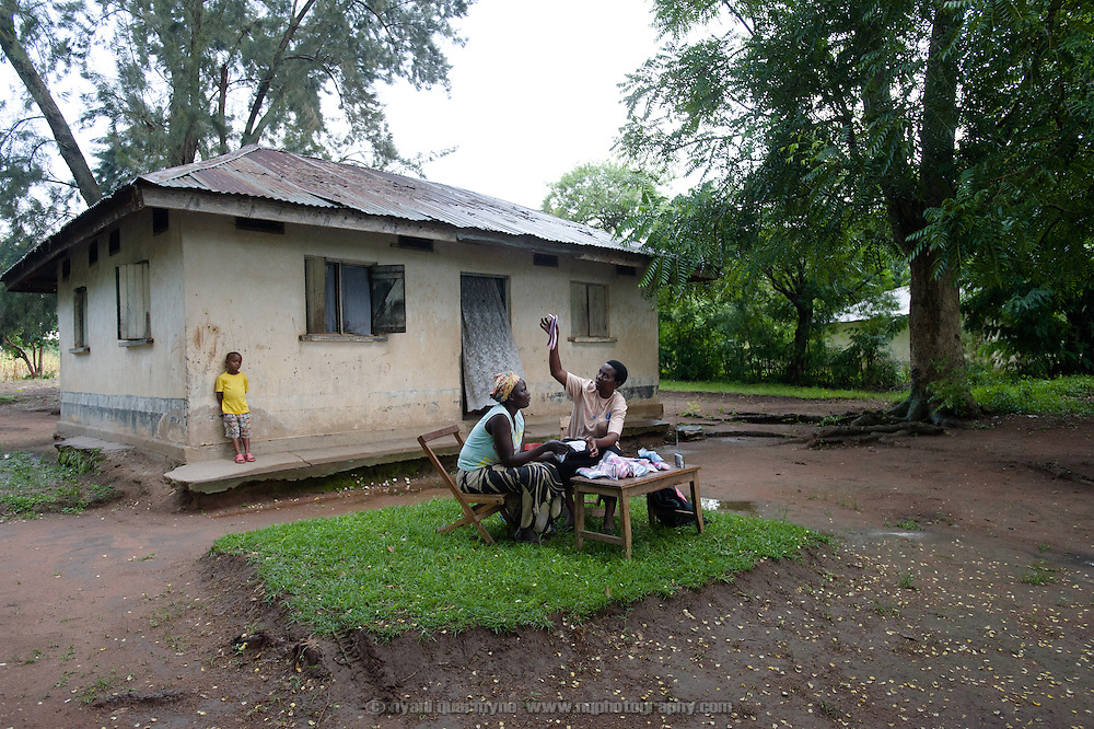 "Lovisa Wankya, a teacher and an Afripads dealer, in front of her home near Tororo in Eastern Uganda, explaining to Caroline Adongo how Afripads should be dried in the sun, on 1 August 2014. Having heard of Afripads and ""Madam Wankya"" on the radio, Caroline was interested in them, but didn't know how to contact Lovisa. She happened to be passing by, and was excited to meet ""Madam Wankya"" and learn about Afripads. She decided to buy two kits, one for herself and one for her daughter. (Afripads are reusable fibre sanitary pads that are having a revolutionary impact on menstrual hygiene management, particularly amongst girls and women who cannot afford expesive disposable pads, and who previously had to use rags, cotton wool or toilet paper.)"