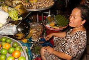 An older lady preparing fruit and vegetables for sale in the Ben Thanh Market, Saigon Vietnam.