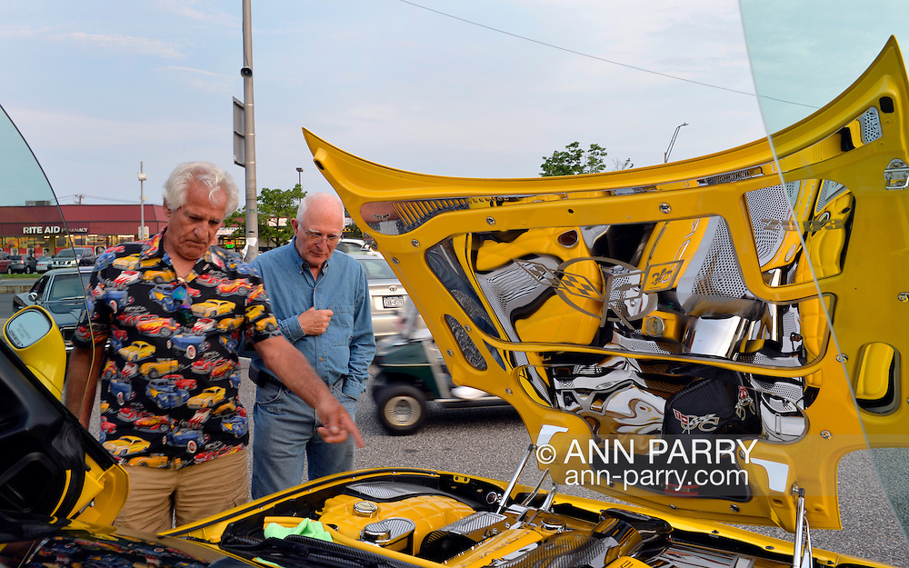 Bellmore, New York, USA. 12th June 2015. Two senior men, one man pointing to engine, look at a modified yellow 2003 Corvette 50th Anniversary model, with Lamborghini doors (AKA vertical scissors doors and Lambo doors) whose glass is visible at each side, and chrome trim added to inside of hood to reflect engine, an award winning car owned by Grey Cherveny of Bay Shore, is displayed  at the Friday Night Car Show held at the Bellmore Long Island Railroad Station Parking Lot. Hundreds of classic, antique, and custom cars were on view at the free weekly show, sponsored by the Chamber of Commerce of the Bellmores.