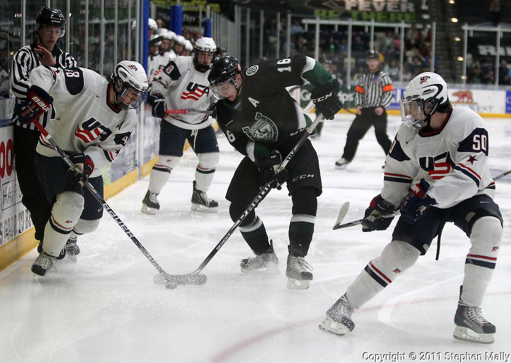 Team USA's Brady Skjei (48), RoughRiders' Michael Parks (16), and Team USA's Cameron Darcy (50) battle for control of the puck during the first period of the game between the Cedar Rapids RoughRiders and Team USA at the Cedar Rapids Ice Arena at 1100 Rockford Road SW in Cedar Rapids on Saturday evening, April 9, 2011. RoughRiders won 4-2.