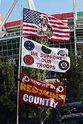 """A Washington Redskins flag, a """"We Support Our Troops"""" flag, and an American flag with an indian on it fly in the breeze before the Washington Redskins 2016 NFL week 1 regular season football game against the Pittsburgh Steelers on Monday, Sept. 12, 2016 in Landover, Md. The Steelers won the game 38-16. (©Paul Anthony Spinelli)"""