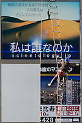 A workman puts up posters on an advertising billboard below an existing billboard for the Church of Scientology,. Shibuya, Tokyo, Japan. Friday January 13th 2017