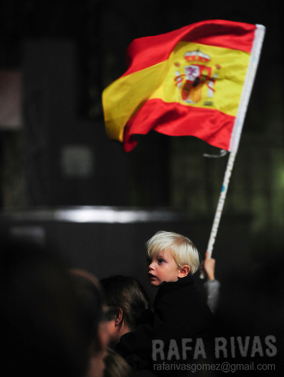 A Spanish flag is waved next to a child as faithful wait for Pope Benedict XVI's arrival in front of the Archbishop's palace of Barcelona on November 6, 2010 during his two-day visit in Spain. Benedict XVI warned today of a very strong clash between faith and modernity in Spain and he called for dialogue, not confrontation. The pontiff said an anti-clerical movement erupted in Spain in the 1930s in the run-up to the Spanish Civil War.  Photo Rafa Rivas