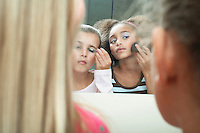 Girls looking in mirror applying make-up and mascara