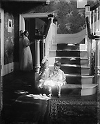 Lollipops': Posed photograph of two small girls sitting at the bottom of the stairs in a shaft of sunlight,  sucking lollipops, while a woman watches from a doorway.  Waban, Mass.  Children in domestic interior, c1910.