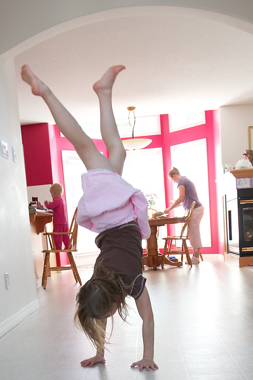 Claire demonstrates her handstand in the front hall.