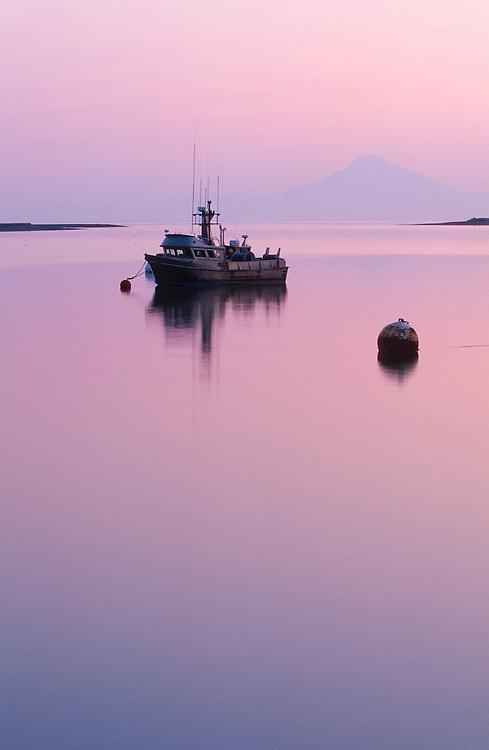 Alaska. Kenai Peninsula. Sunset over Redoubt Mt. Volcano across Cook Inlet.  Kenai River salmon commercial fishing boat.