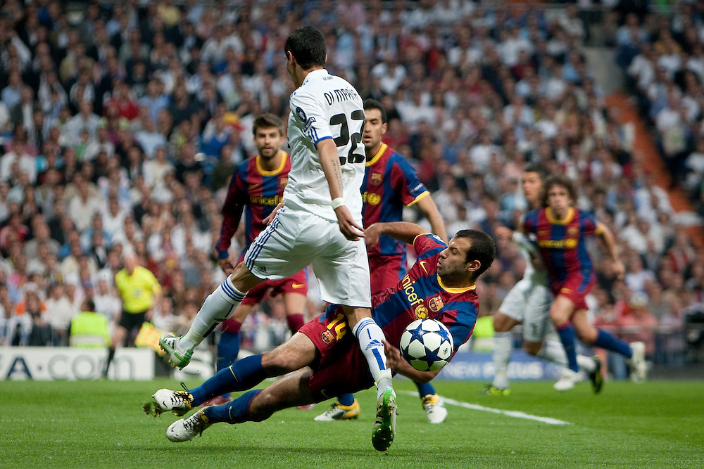 Real Madrid's Angel Di Maria from Argentina, left, vies for the ball with Barcelona's Javier Mascherano from Argentina, right, during their semi final, 1st leg, Champions League soccer match at the Santiago Bernabeu stadium in Madrid, Wednesday, April 27, 2011.