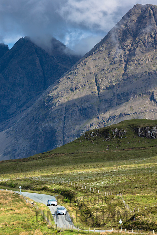 Tourists visiting Cuillin mountain range during touring holiday on Isle of Skye in the Highlands and Islands of Scotland