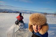snowmobile in Northern Finlandboy with furhead in Finland