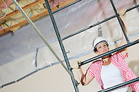 Young female construction worker climbing on scaffold