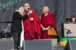 © Licensed to London News Pictures. 28/06/2015. Pilton, UK.  The Dalai Lama on the Glastonbury Festival Pyramid stage with Patti Smith  on Sunday Day 5.   Patti reads a poem to the Dalai Lama for his birthday, he joins her on stage, the audience sing him happy birthday, he blows candles out on his cake which he then cuts, before giving a speech to the audience.  This years headline acts include Kanye West, The Who and Florence and the Machine, the latter being upgraded in the bill to replace original headline act Foo Fighters.  Photo credit: Richard Isaac/LNP