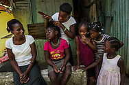 SAN LUIS, THE DOMINICAN REPUBLIC - June 25, 2015: Girls get their hair braided in Batey Naranjo, an impoverished community of sugar cane workers of primarily Haitian descent, on the outskirts of Santo Domingo. Approximately 90 percent of the batey's residents lack citizenship documents and live on less than five dollars a day.