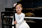 young Asian girl posing sitting by a piano