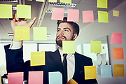 Creative businessman working with stocky notes on glass wall in office