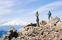 A woman posing for a picture atop the summit of Sauk Mountain in the North Cascades of Washington State, USA.  Mt Naker in the background.