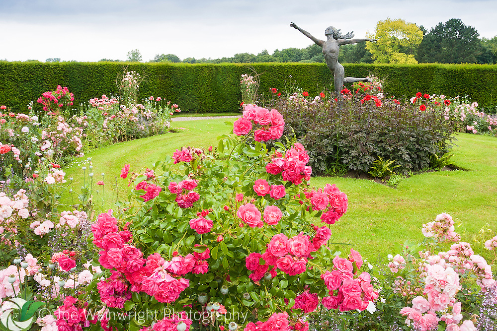 A delicately poised statue of a wood nymph rises above the roses and dahlias in the Rose Garden at Rode Hall, Cheshire.