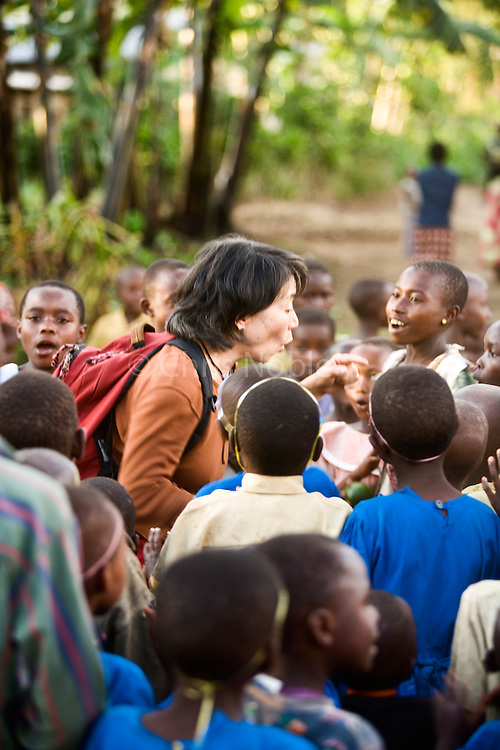 Lily Yeh, founder of Barefoot Artists, playing with Children in the Genocide Survivors Village, of Rugerero Rwanda. Lily and her organization the Barefoot Artists have used community art to bring aid and development to the village.