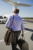 Senior businessman going towards airplane on landing strip.