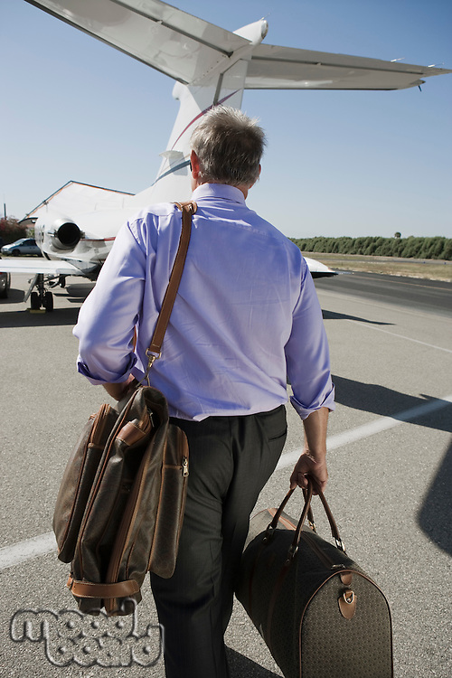 Senior businessman going towards airplane on landing strip.