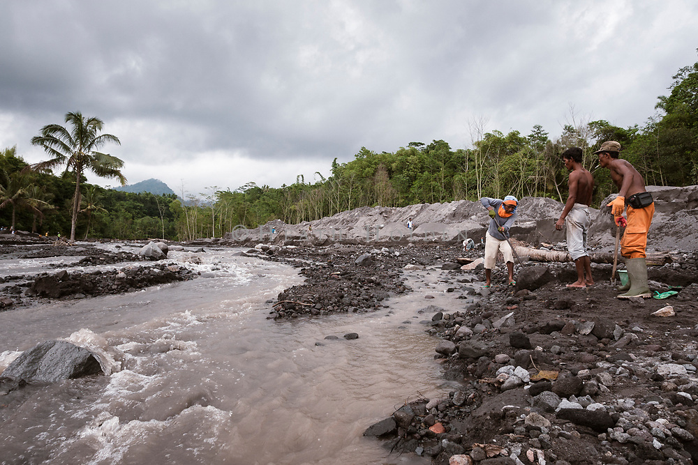 Men collect rocks washed down to the Sabo dam after the 2010 Mt Merapi eruption.