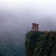 "Mountain Biking on Death Road, Bolivia...A tour group of young British and Australian tourists celebrate their success of completing the 64 kilometer journey mountain biking down the infamous narrow dirt road by posing nude for a photograph on a landmark bend of the road...The North Yugas Road is a 64 Kilometer road leading from La Paz to Corioico. It is legendary for it's extreme danger and in 1995 the Inter American Development Bank christened is as the ""world's most dangerous road"".. The road was built in the 1930's during the Chaco War by Paraguayan prisoners to connect the Amazon rainforest region of Northern Bolivia to it's capital City La Paz. One estimate is that 200 to 300 travelers were killed yearly along the road. On 24 July 1983, a bus veered off the Yungas Road and into a canyon, killing more than 100 passengers in what is said to be Bolivia's worst road accident..A new stretch of the La Paz-Coroico highroad was opened in 2006 to bypass the notorious stretch known as death road..The danger of the road has now made it a popular tourist destination starting in the 1990's and drawing thrill-seekers and mountain bike enthusiasts who ride on the 64km mainly downhill stretch from La Cumbre, a 4,700 meter peak to Yolosa, a decent of 3600 meter's (11,800 feet). The journey includes breathtaking views of snow covered peaks and towering cliffs and starts along modern asphalted road before entering the jungle itself and the most dangerous and notorious part of the ride. The infamous narrow dirt road, most of the road no wider than 3.2 meter's, is cut into the side of the mountain with sheer drops to the left of up to 600 meter's with virtually no safety rails on the winding steep decent..There are now many tour operators catering to this activity, providing information, guides, transport and equipment. Nevertheless, the Yungas Road remains dangerous. At least 13 of these cyclists died on the ride since 1998, the latest A 28-year-old Israeli traveler was killed in"