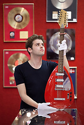 © Licensed to London News Pictures. 28/06/2013. London, UK. A Bonhams employee holds a cardinal red 'Vox' twelve string electric guitar (est. GB£10,000-15,000) used by David Bowie during the promotion of his 1972 album 'The Rise and Fall of Ziggy Stardust and the Spiders from Mars' in London today (28/06/2013) at the press view for an entertainments auction being held at Bonham's Knightsbridge premises on the 3rd of July 2013. Photo credit: Matt Cetti-Roberts/LNP