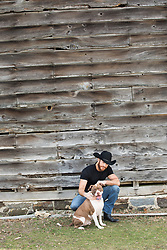 sexy cowboy with a rescue dog by a barn