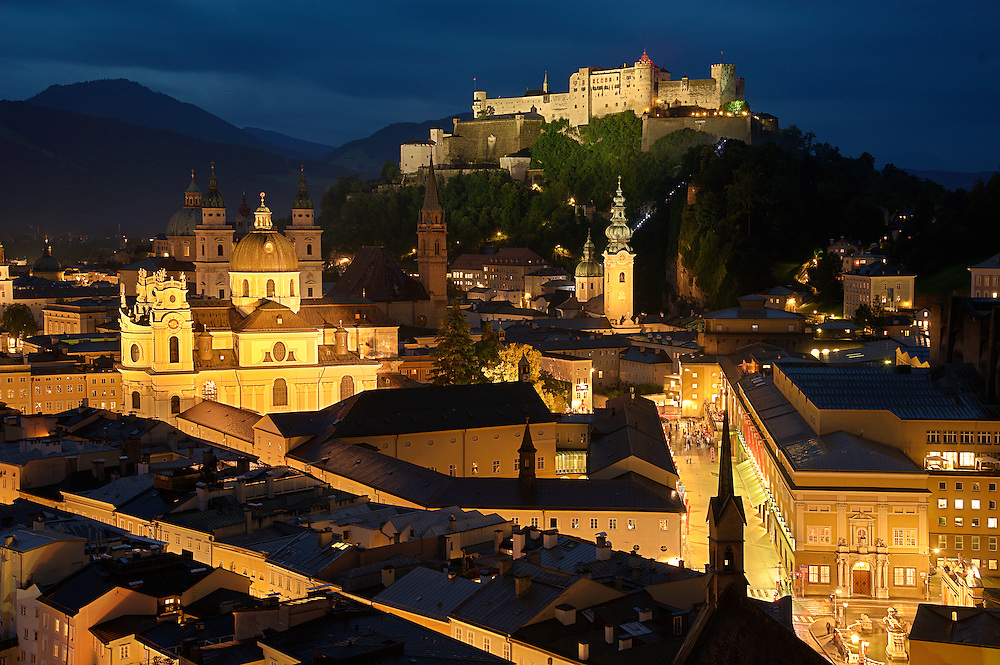 Evening in Salzburg.  The Hohensalzburg Fortress dominates the Old Town from its perch on the Festungberg.  To the left, the brightly lit University of Salzburg Church stands in front of Salzburg's cathedral.  The onion-domed St. Peter's Church stands just below the fortress.